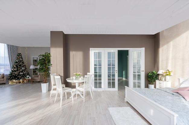 밝은 색상의 고급스러운 고가의 아파트 인테리어. 세련되고 현대적인 미니멀리즘 디자인. 태양 빛이 가득합니다. 크리스마스 트리로 장식 된 많은 공간
