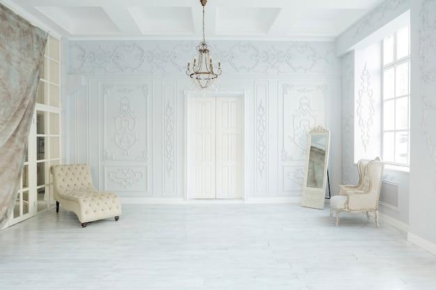 우아한 클래식 가구와 벽 장식으로 고급스러운 거실 인테리어 디자인. 큰 창문이있는 크고 밝은 흰색 방