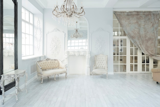 エレガントでクラシックな家具と壁の装飾が施された豪華で豊かなリビングルームのインテリアデザイン。大きな窓のある大きな明るい白い部屋