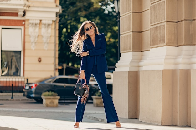 Luxury rich woman dressed in elegant stylish blue suit walking in city on sunny autumn day holding purse