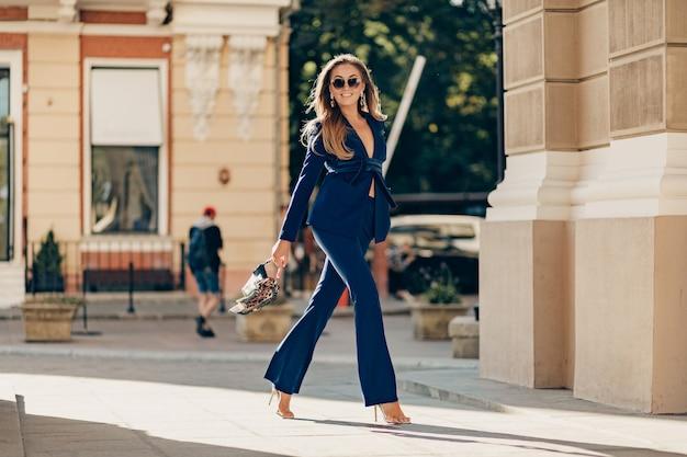 La donna ricca di lusso si è vestita in vestito blu alla moda elegante che cammina nella città il giorno soleggiato di autunno che tiene la borsa