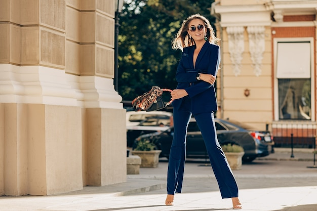 Luxury rich woman dressed in elegant stylish blue suit walking in city on sunny summer day holding purse