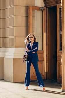 Роскошная богатая женщина, одетая в элегантный стильный синий костюм, гуляет по городу в солнечный осенний день, держа кошелек
