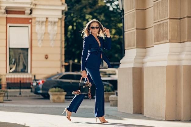 Роскошная богатая женщина, одетая в элегантный стильный синий костюм, гуляет по городу в солнечный летний день, держа кошелек