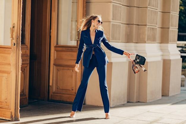 지갑을 들고 화창한 여름 날에 도시에서 걷는 우아한 세련된 파란색 정장을 입고 럭셔리 풍부한 여자