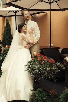 古い日当たりの良い街を背景に結婚を祝う豪華なロマンチックな幸せな新郎新婦
