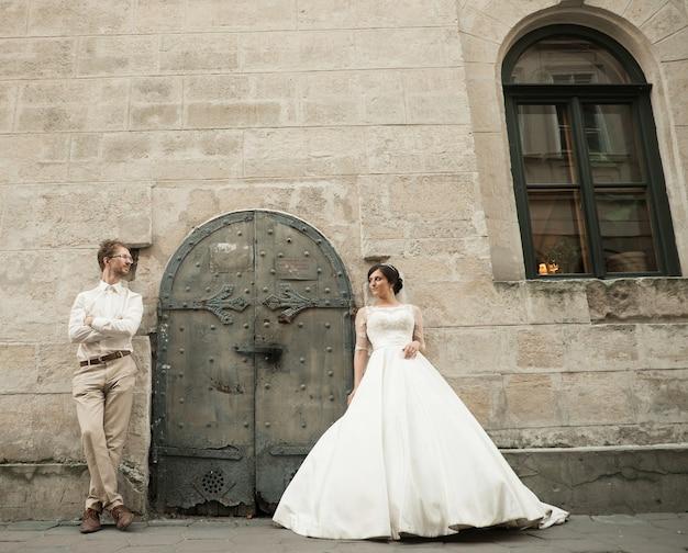 Роскошный романтический счастливый жених и невеста празднуют брак на фоне старого солнечного города