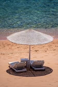 아프리카 이집트 홍해 연안의 열대 리조트에 해변 의자와 흰색 짚 우산이 있는 고급 모래 해변. 검역 중 빈 해변