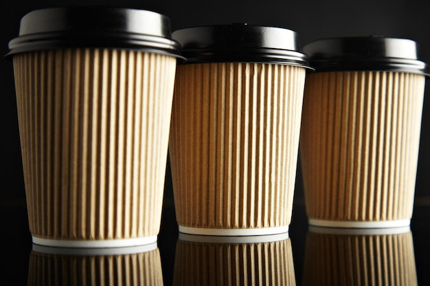 Luxury set of brown take away cardboard paper cups closed with caps isolated on black and mirrored. retail  presentation