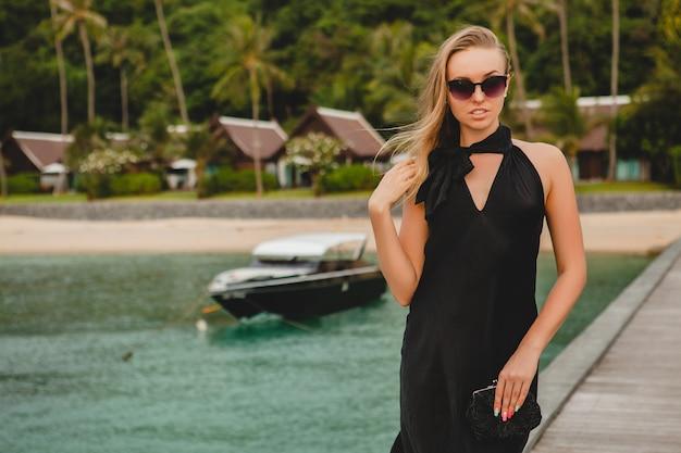 Donna attraente sexy di lusso vestita in abito nero in posa sul molo in hotel resort di lusso, indossando occhiali da sole, vacanze estive, spiaggia tropicale