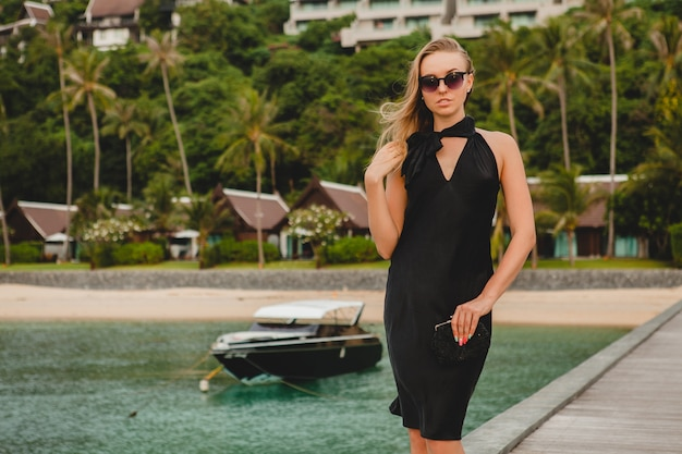 Luxury sexy attractive woman dressed in black dress posing on pier in luxury resort hotel, wearing sunglasses, summer vacation, tropical beach