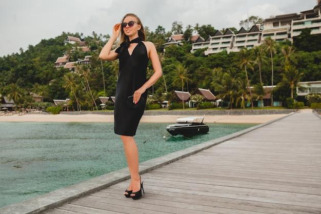 Роскошная сексуальная привлекательная женщина, одетая в черное платье, позирует на пирсе в роскошном курортном отеле, в солнцезащитных очках, летние каникулы, тропический пляж