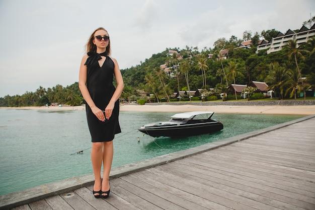 黒のドレスに身を包んだ豪華なセクシーな魅力的な女性が高級リゾートホテルの桟橋でポーズをとって、サングラスをかけて、夏休み、熱帯のビーチ