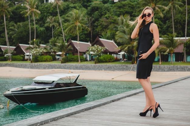 럭셔리 리조트 호텔에서 부두에 포즈 검은 드레스를 입고 럭셔리 섹시 매력적인 여자, 선글라스를 착용, 여름 휴가, 열대 해변