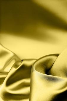 テキストのための場所と豪華な滑らかな金色のシルクの背景のモックアップ