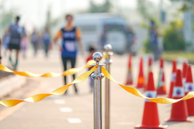 フィニッシュポイントでのマラソンイベントの道路上の黄色いロープリボン付きの豪華なステンレスバリケード。