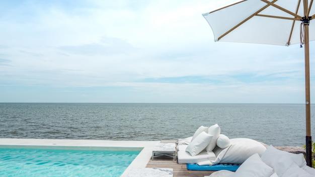 Роскошный бассейн и голубая вода на курорте с прекрасным видом на море.