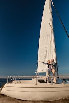 帆船やヨットのデッキの横に立っている幸せな成熟したカップルの豪華な旅行の全長