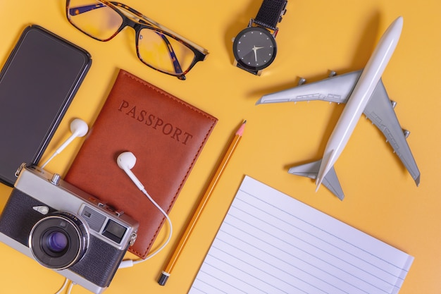 Luxury travel objects flatlay on yellow top view