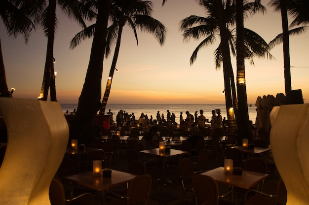 Luxury tropical beach restaurant with people at sunset. philippines