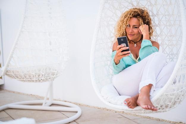 電話デバイスと白い椅子に座って休んでいる屋外のレジャー活動を楽しんでいる美しい大人の白人のブロンドの女性との贅沢な休暇のライフスタイルのコンセプト