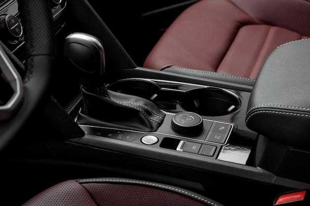 Роскошный салон автомобиля с красными кожаными сиденьями. кнопка старт-стоп и рычаг автоматической коробки передач