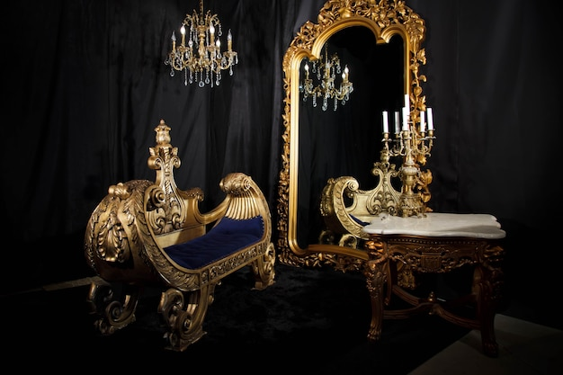 Luxury vintage home room interior in black and gold. living room with mirror, sofa and candelabra. antique background with elegant furniture. concept of vintage. copyright space for site or banner