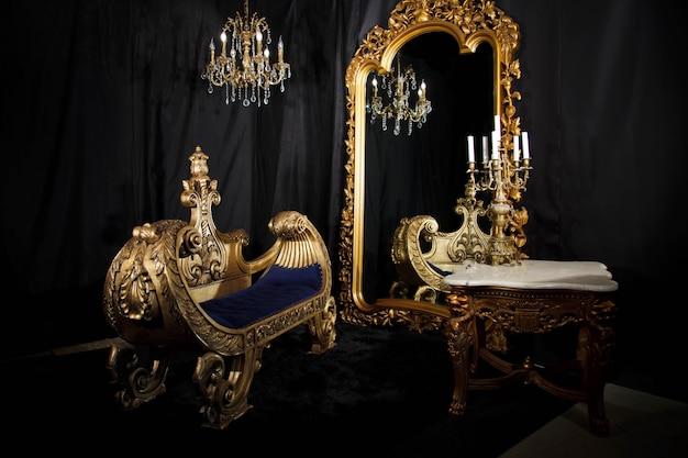 黒と金の豪華なヴィンテージの家の部屋のインテリア。鏡、ソファ、燭台のあるリビングルーム。エレガントな家具とアンティークの背景。ヴィンテージのコンセプト。サイトまたはバナーの著作権スペース