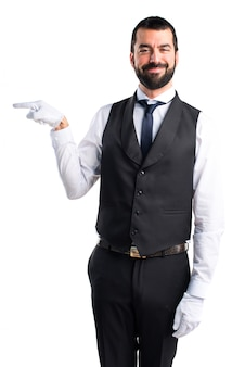 Luxury waiter pointing to the lateral