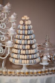 豪華な結婚式のキャンディーバーテーブルセット。マカロンタワーまたはピラミッドと甘いデザートテーブルのカップケーキ。パステルのスタイリッシュな色、お菓子、おやつ
