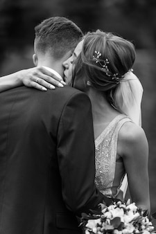 抱き合って、日当たりの良い光の中でキスを受け入れる豪華な結婚式のカップル。官能的な優しい感情の瞬間にゴージャスな花嫁とスタイリッシュな新郎。黒白の写真。