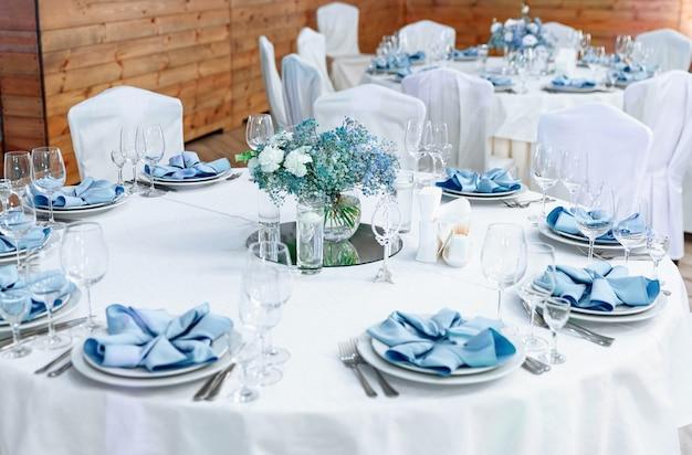 豪華な結婚式のテーブルの装飾。白いテーブルクロス、生花、優しい青いナプキンを使ったスタイリッシュで美しいウェディングテーブルサービス。イベントパーティーのテーブルセッティング。