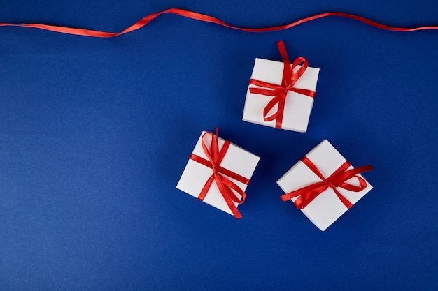 Luxury white gift boxes with red ribbon on blue
