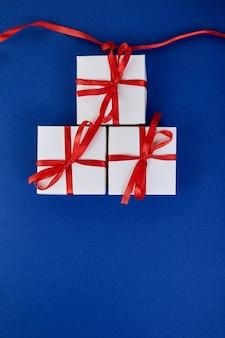 Роскошные белые подарочные коробки с красной лентой на синем фоне тренда цвета. день святого валентина, рождество, подарки на день рождения. квартира лежала. вид сверху.