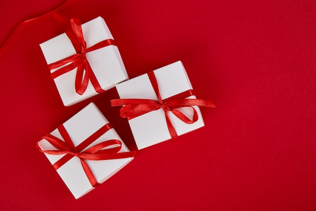 Роскошные белые подарочные коробки с красной лентой на красном фоне. день святого валентина, рождество, подарки на день рождения. день матери или женщины. квартира лежала. вид сверху.
