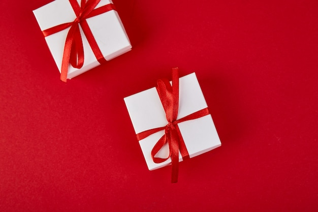 Luxury white gift boxes with red ribbon on red background.