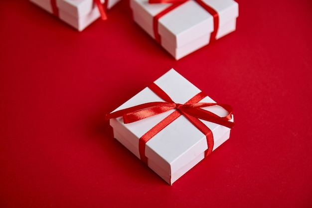 Luxury white gift boxes with red ribbon on red.