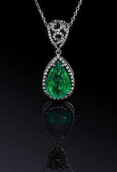 Luxury white gold pendant with big natural green emerald and diamonds isolated on black background with reflection, included clipping path. extreme close up.
