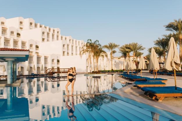 고급스러운 흰색 호텔 이집트, 동부 스타일, 멋진 큰 수영장이있는 리조트. 예쁜 여자, 수영장 중간에 포즈 검은 수영복을 입고 모델. 휴가, 휴가, 여름.
