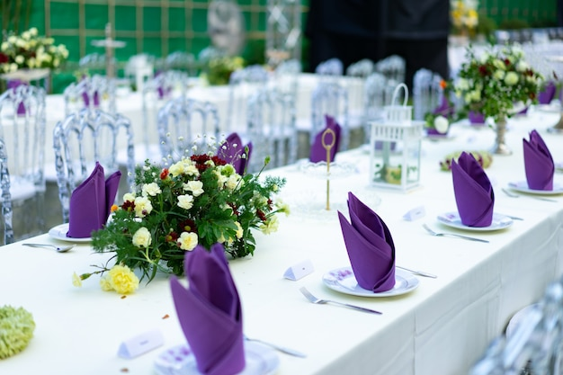 Luxury white - purple - red dinner table set with crystal chair in the garden.
