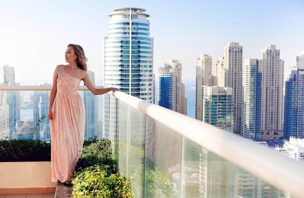두바이 마리나 고층 빌딩이 보이는 옥상 파티에서 호화로운 여성