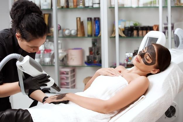 Роскошная женщина в спа-салоне с угольной маской на лице и косметолог, работающий над ее рукой с лазерным аппаратом, уход за телом и уход за кожей
