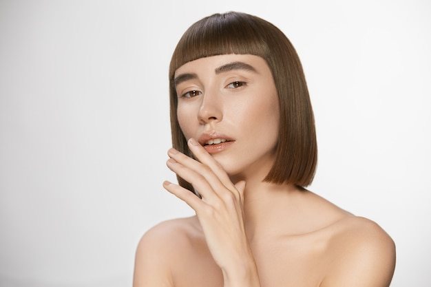 Luxury woman with fresh clean skin and stylish haircut with bangs, sensual pretty woman touching her glossy lips having nude daily make-up and shiny straigh hair