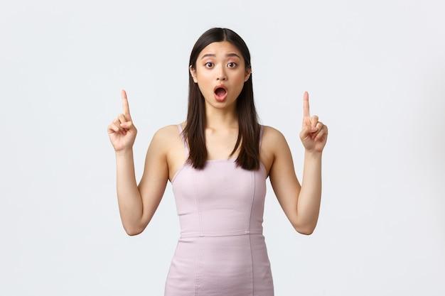 贅沢な女性、パーティー、休日のコンセプト。ベージュのイブニングドレス、指を上に向けて、ウエディングナイトの女の子に驚いて心配しているかわいいアジアの女性