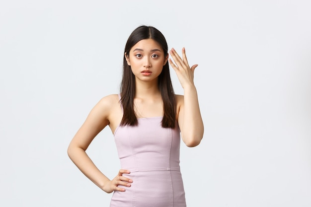 贅沢な女性、パーティー、休日のコンセプト。イブニングドレスを着て、頭を指してイライラしているように見えるイライラした若いアジアの女性は、不平を聞いてうんざりし、白い背景に立っています。