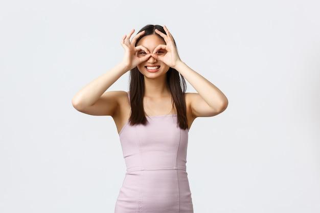 贅沢な女性、パーティー、休日のコンセプト。イブニングドレスでのんきな美しいアジアの女の子、目の上の指と笑顔で偽のメガネを作る