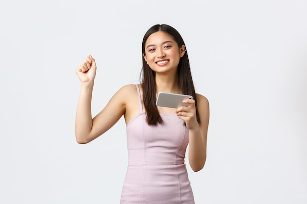 贅沢な女性、パーティー、休日のコンセプト。チャンピオンのように踊り、ゲームで勝ち、携帯電話で遊ぶ陽気で喜んでいるハンサムなアジアの女の子