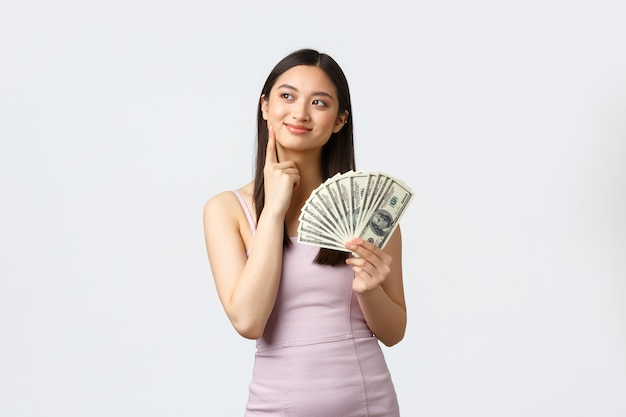 贅沢な女性、パーティー、休日のコンセプト。すべてのお金を無駄にする方法を考えている夢のような金持ちの若いアジアの女性は、余分な現金を手に入れました
