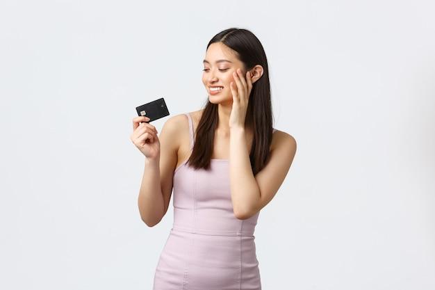 고급 여성, 파티 및 휴일 개념. 모든 돈을 낭비하고 쇼핑을 마친 후 신용 카드에 만족하고 행복해 보이는 바보 같은 아시아 소녀