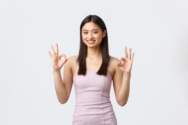 고급 여성, 파티 및 휴일 개념. 괜찮아 기호와 끄덕임 승인을 보여주는 이브닝 드레스에 만족하고 행복 화려한 아시아 소녀